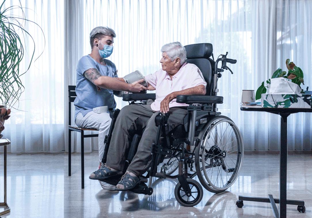 Uno specialista infermieristico qualificato in formazione con maschera facciale misura la pressione sanguigna nella tenda a rullo dell'anziana signora.