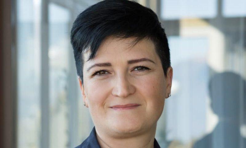 Portrait einer motivierten diplomierten Pflegefachfrau mit kurzen schwarzen Haaren.