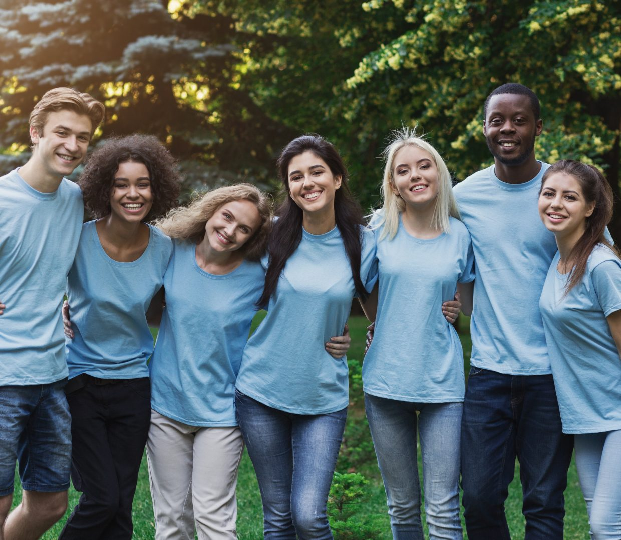 Group Of Young Volunteers Embracing At Park
