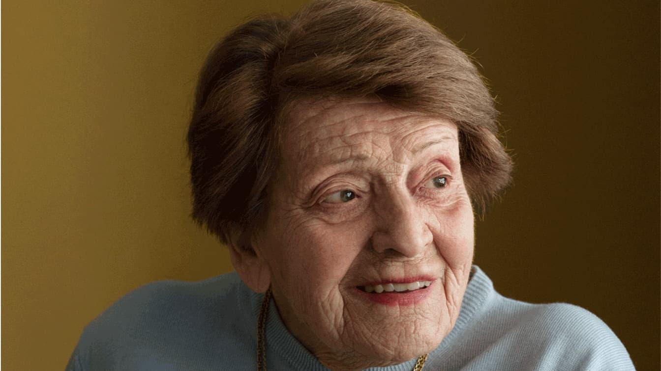 Portrait einer alten Dame mit braunen Harren die lächelt.