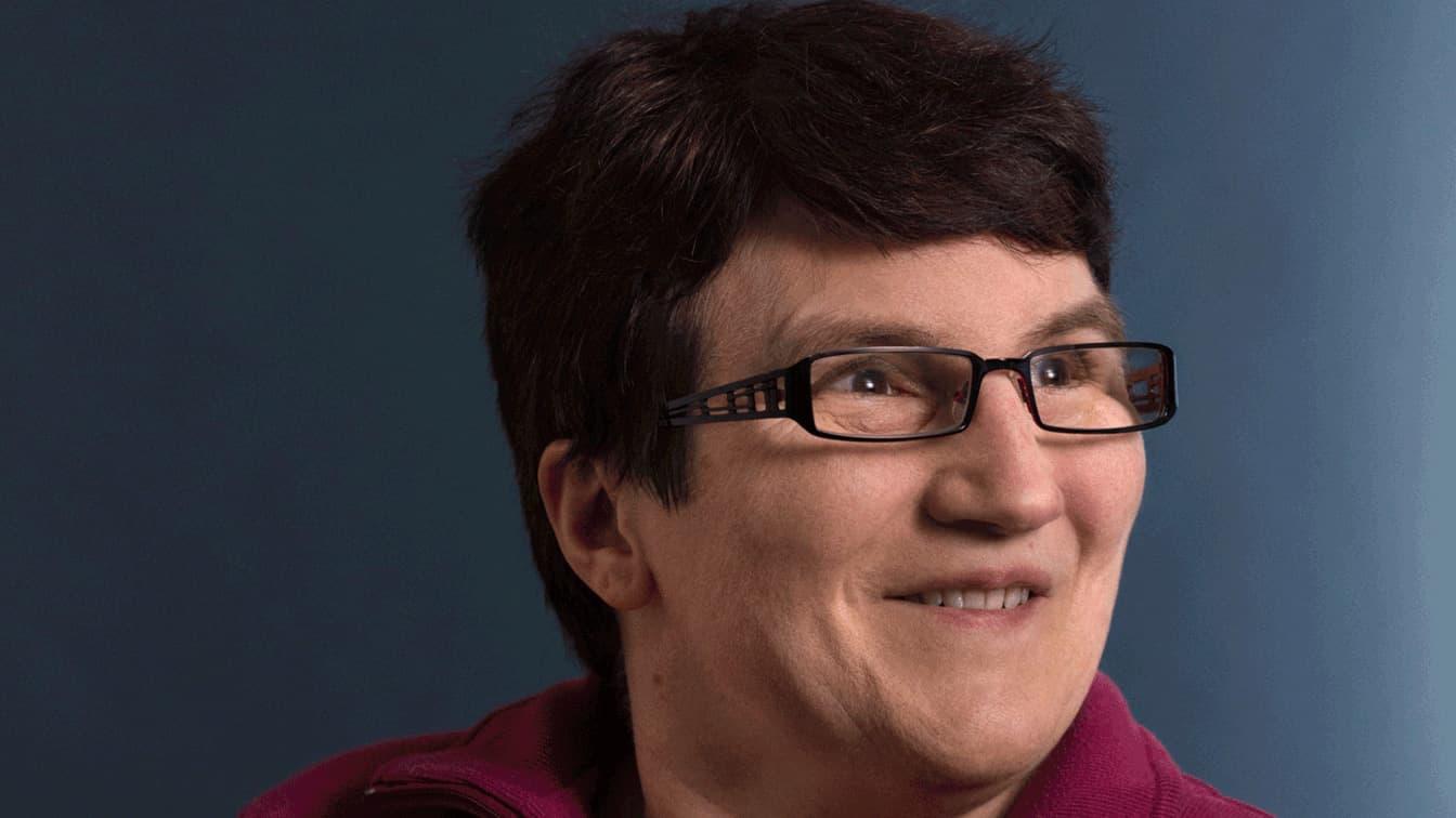 Portrait einer Dame mit braunen Harren und Brille die lächelt.