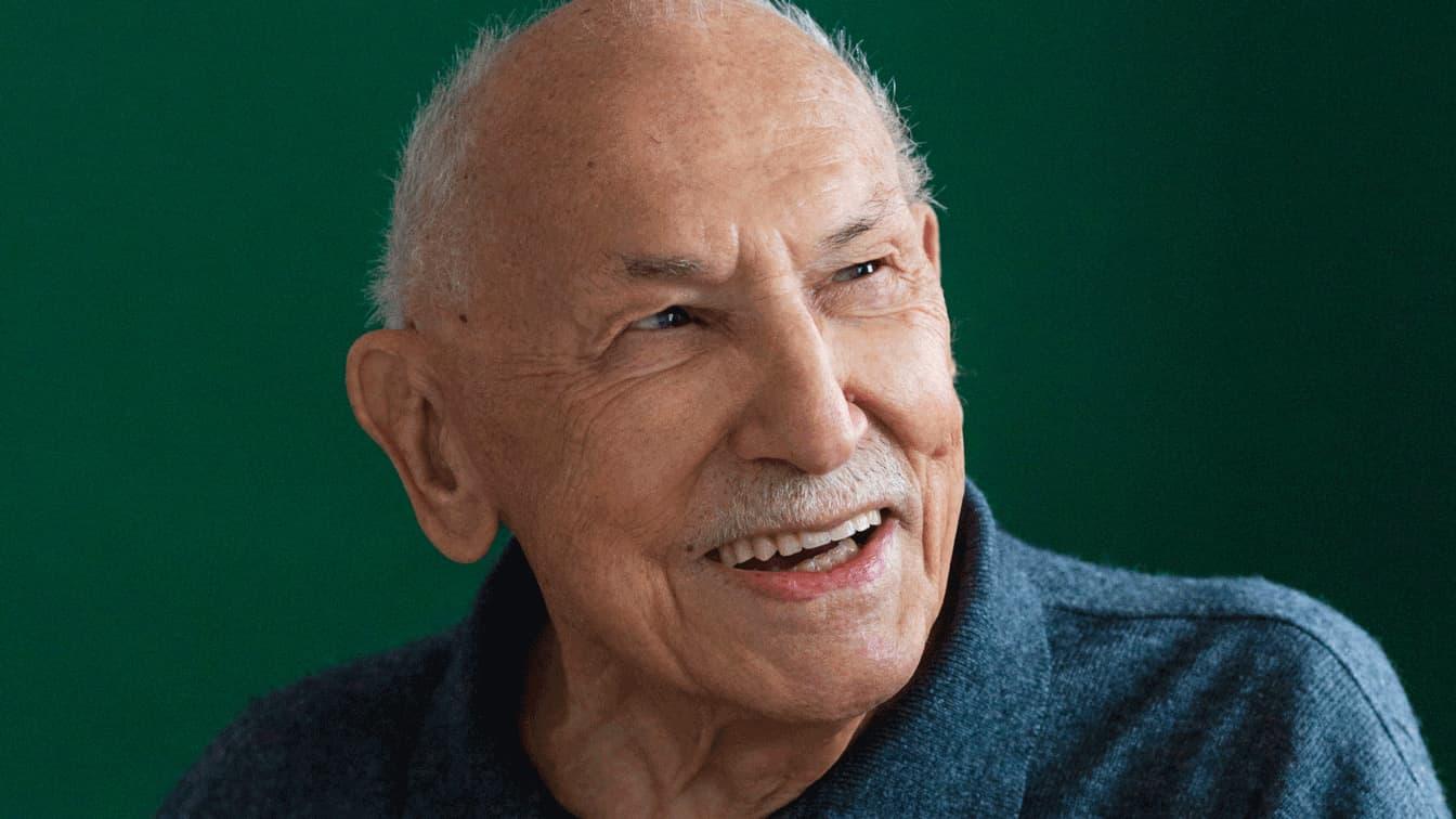 Portrait eines alten Herrn mit wenig weissen Haaren der lächelt.