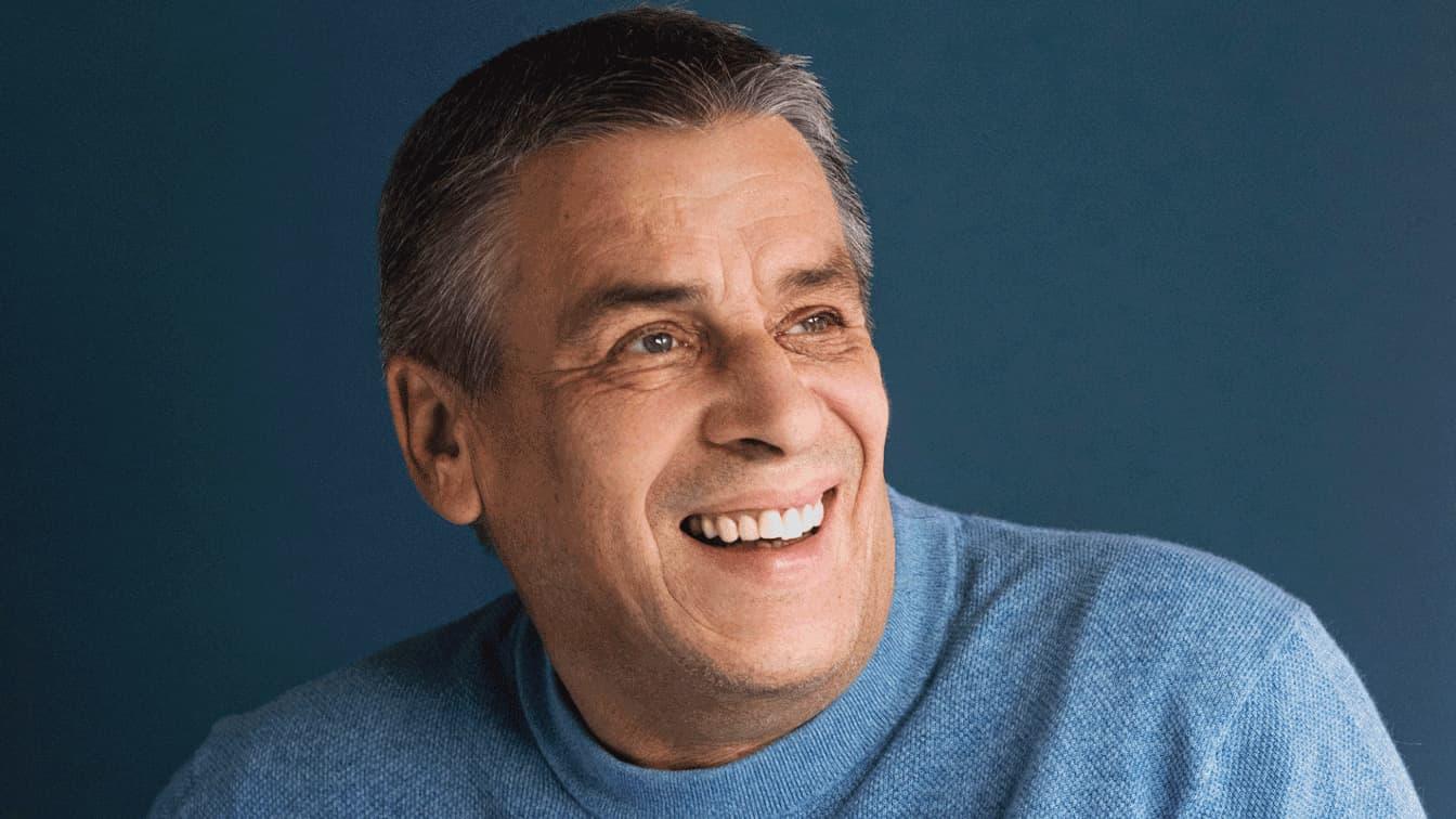 Portrait eines älteren Herrn der lächelt und einen blauen Pullover trägt.