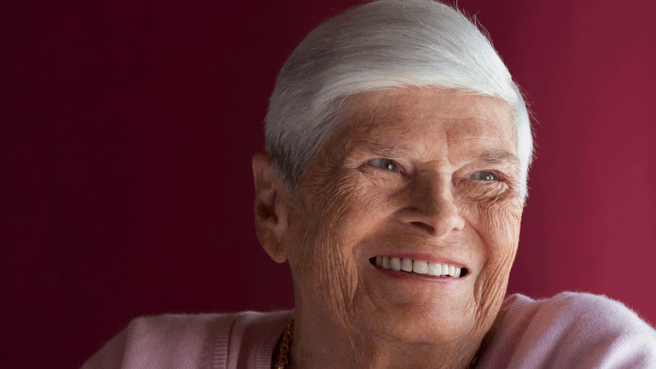 Portrait d'une vieille dame aux cheveux blancs qui sourit.